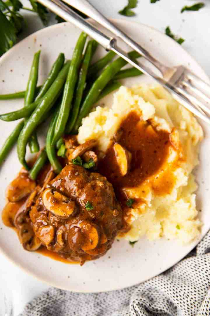 white plate with Salisbury steak, mashed potatoes and green beans
