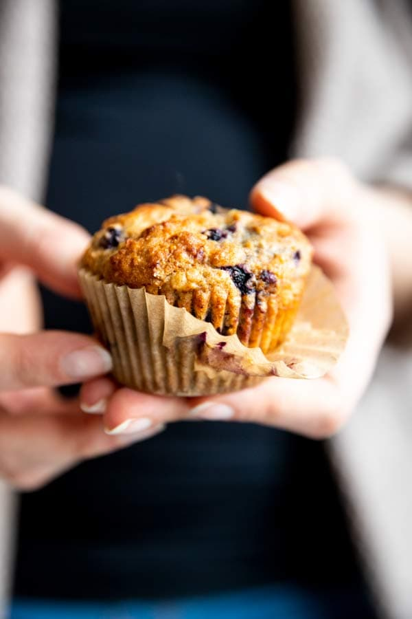 woman holding a blueberry oatmeal muffin