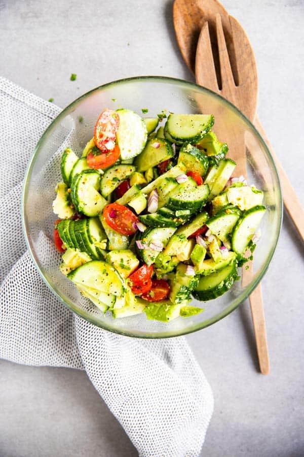 glass bowl with cucumber tomato avocado salad