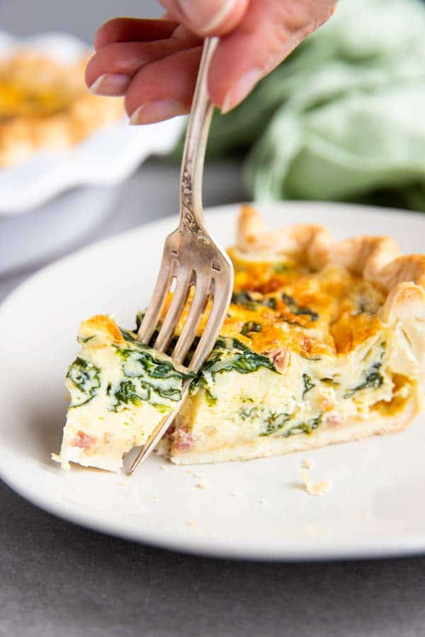fork taking a bite out of a slice of spinach bacon quiche