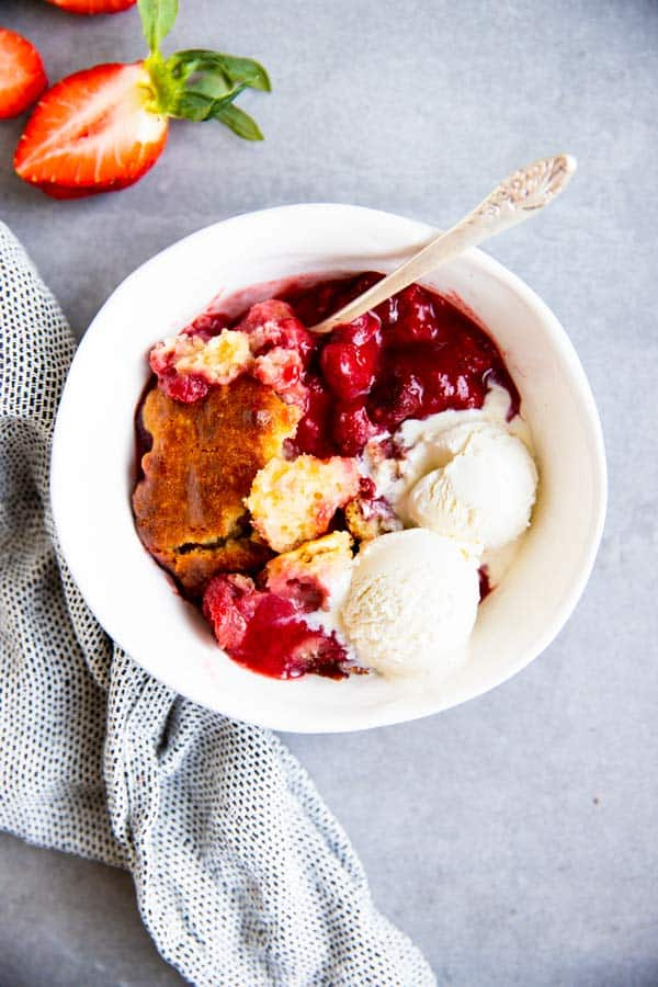strawberry cobbler in a white bowl with ice cream