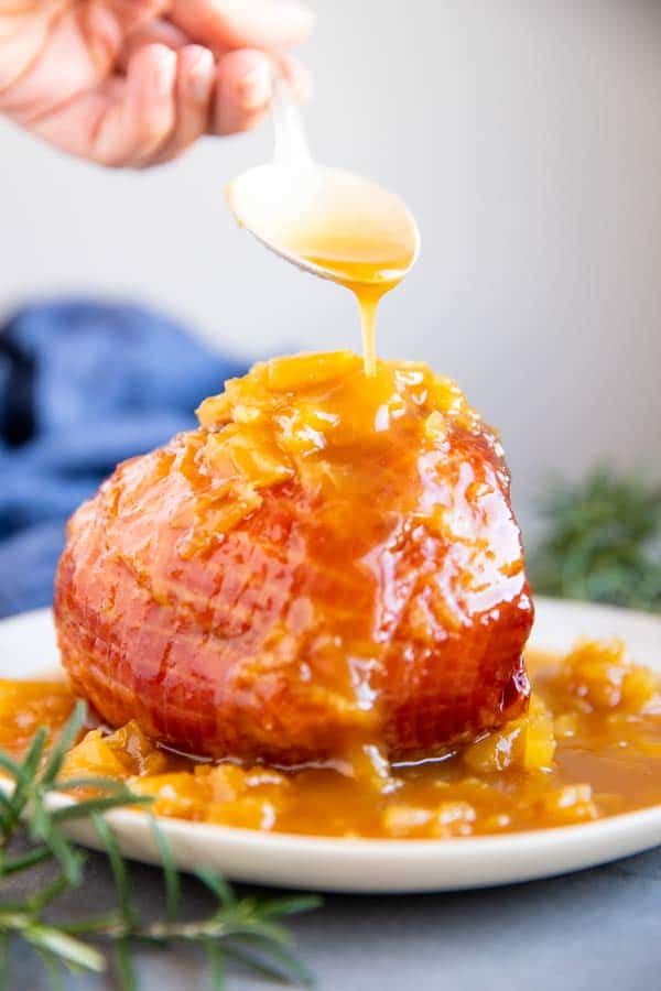 drizzling pineapple glaze over a cooked ham