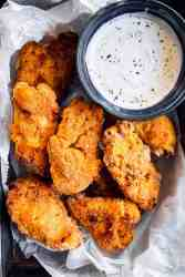 close up photo of buttermilk oven fried chicken on a lined pan