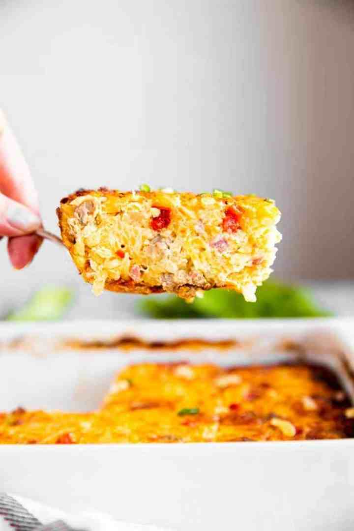 female hand lifting slice of hash brown breakfast casserole out of casserole dish