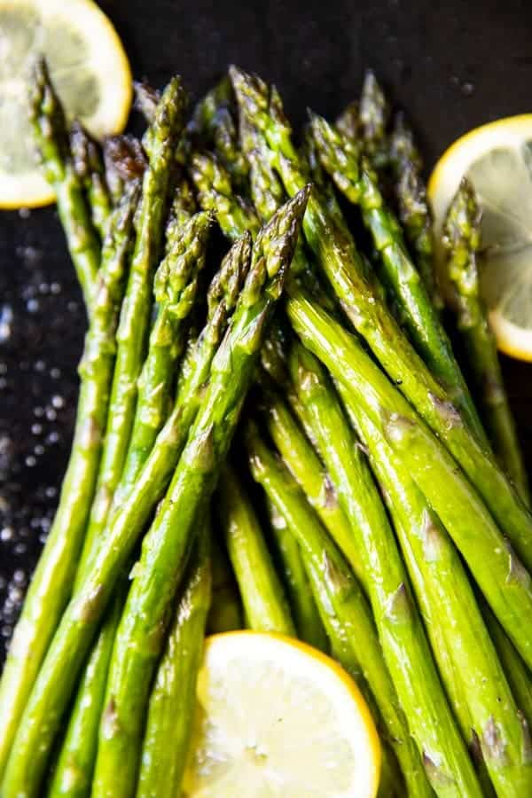 pile of roasted asparagus with lemon slices