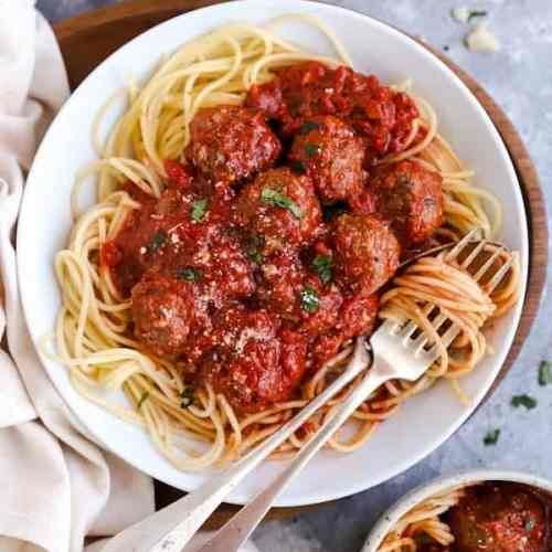 plates and bowls with italian meatballs and spaghetti, next to linen and a block of parmesan cheese
