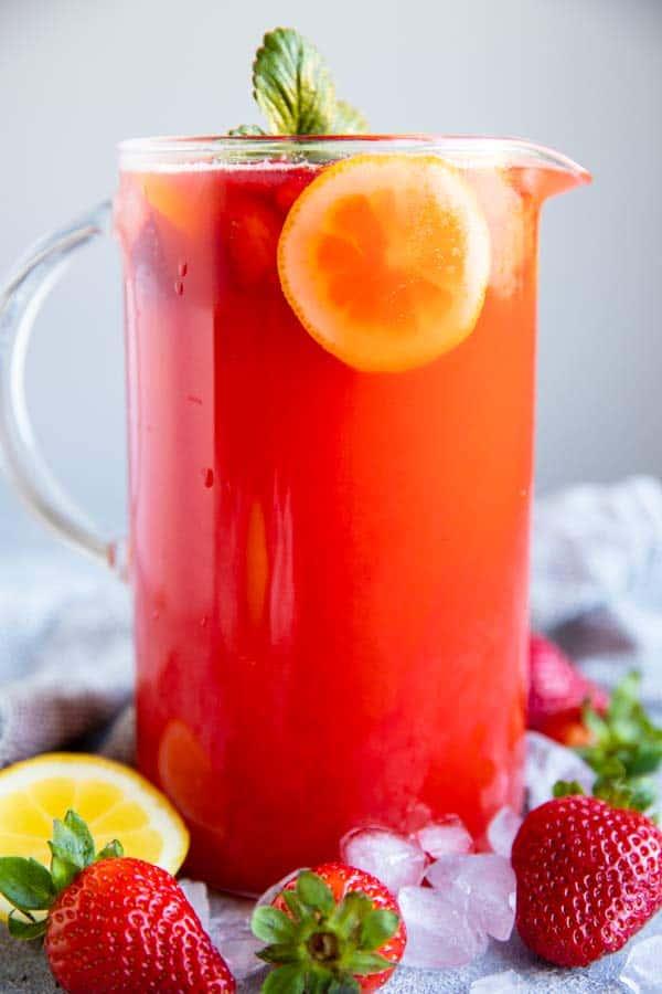 jug with strawberry lemonade, fresh strawberries and lemon slices