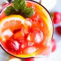 close up photo from the top of a jug with strawberry lemonade