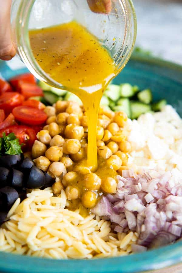 pouring dressing over greek orzo salad