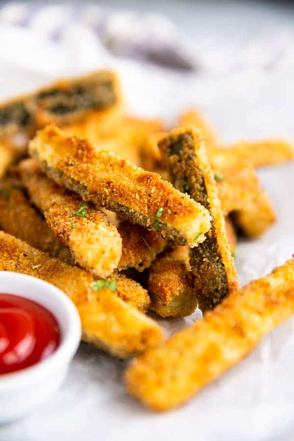 pile of parmesan zucchini fries on a sheet of baking parchment
