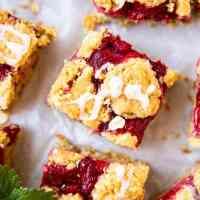 strawberry oatmeal bars with glaze on a sheet of parchment paper