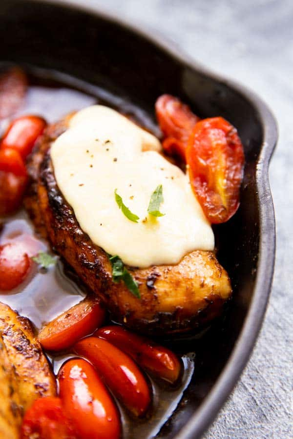 close up photo of a chicken breast in balsamic glaze with tomatoes and mozzarella cheese