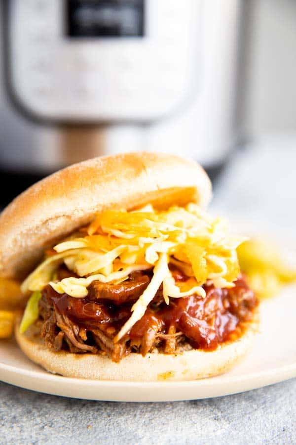 pulled pork sandwich in front of an instant pot pressure cooker