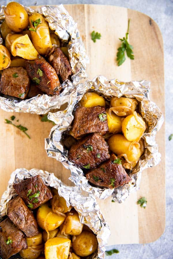 three steak and potato foil packets on a wooden chopping board