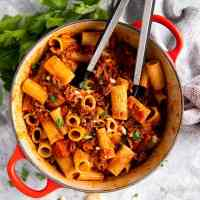 red cast iron pot with rigatoni bolognese and kitchen tongues