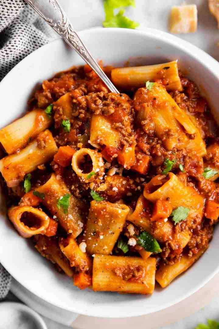 close up photo of rigatoni bolognese in white bowl with fork