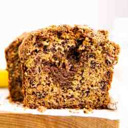 frontal view of a slice of cinnamon crunch banana bread on a wooden board