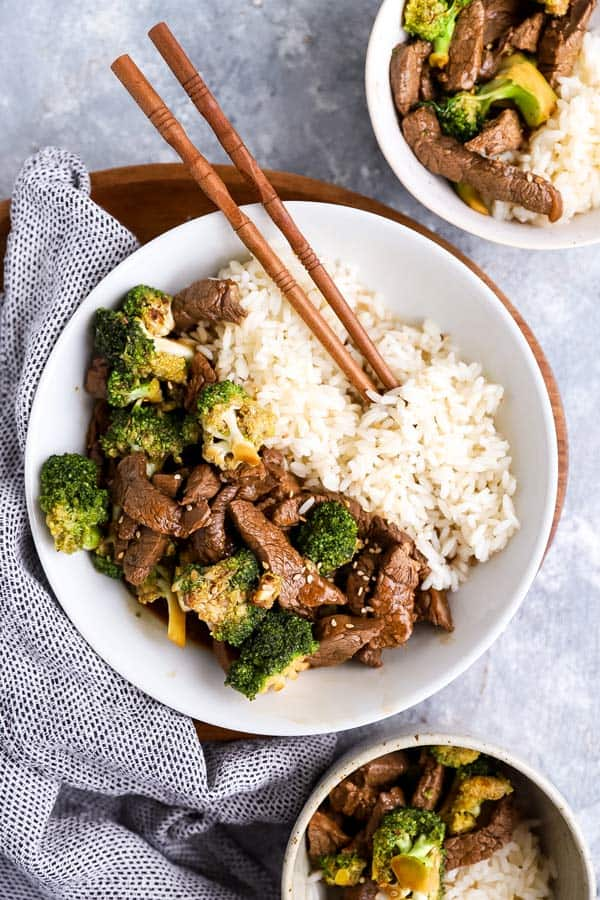 white plate filled with rice, beef and broccoli, with chopsticks