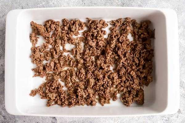 browned ground beef in a white casserole dish
