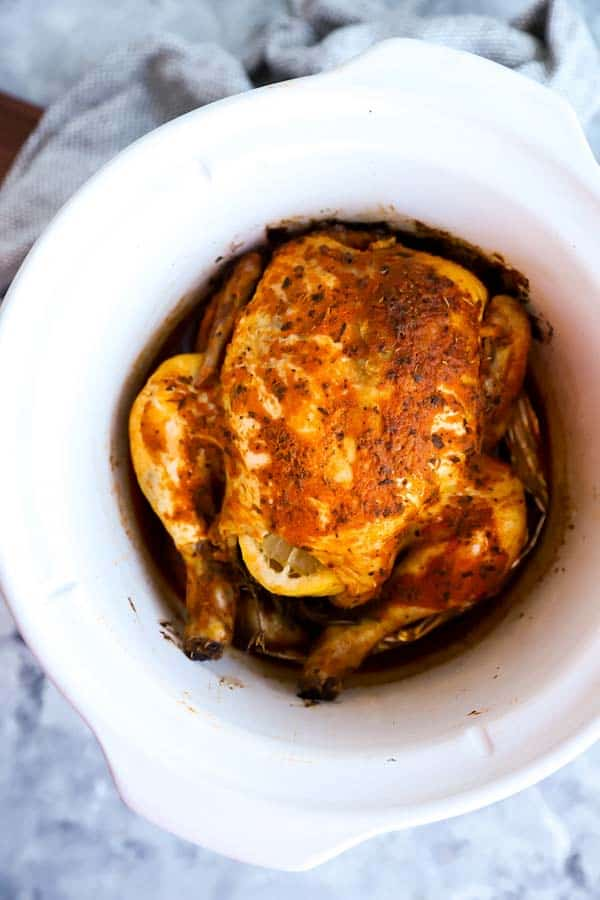Whole seasoned chicken in a white crock of a slow cooker