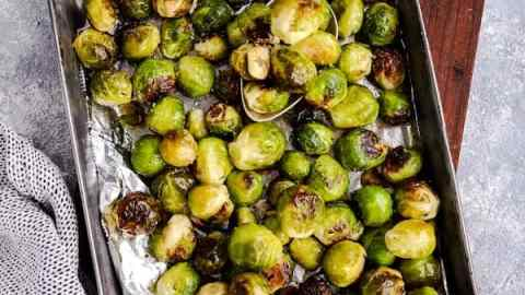 baking pan filled with Brussels sprouts on a wooden board