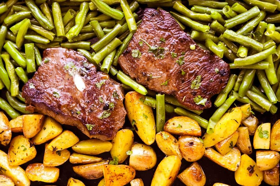 photo of sheet pan with green beans, potatoes and two steaks