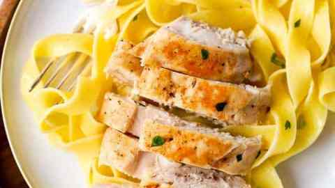 sliced chicken breast on a plate of pasta