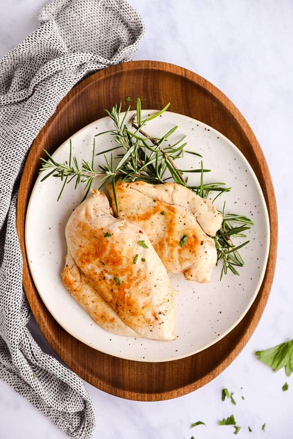 white plate on a wooden platter, with two chicken breasts and rosemary twigs on top