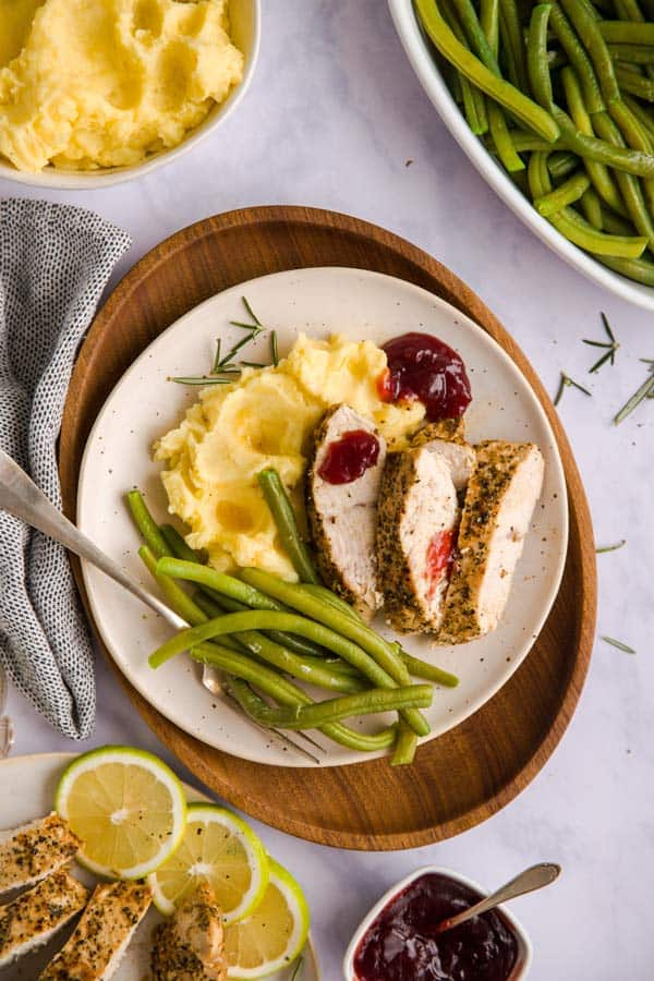sliced turkey breast on a plate with mashed potatoes and green beans