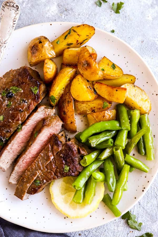 white plate with sliced steak, potato wedges and green beans