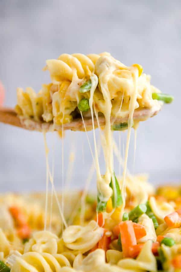 Scooping turkey noodle casserole out of the dish