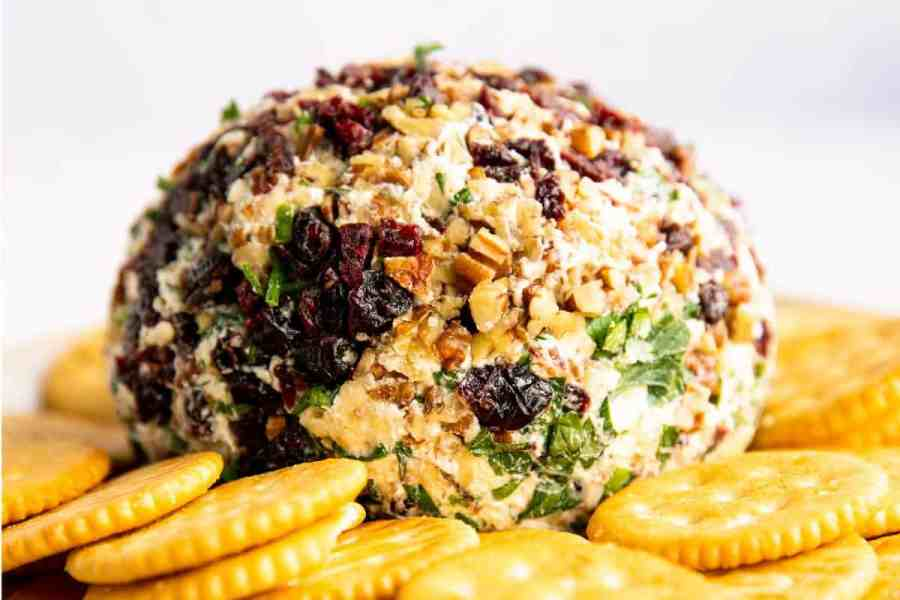 cheeseball rolled in chopped pecans, dried cranberries and parsley sitting on a bed of Ritz crackers