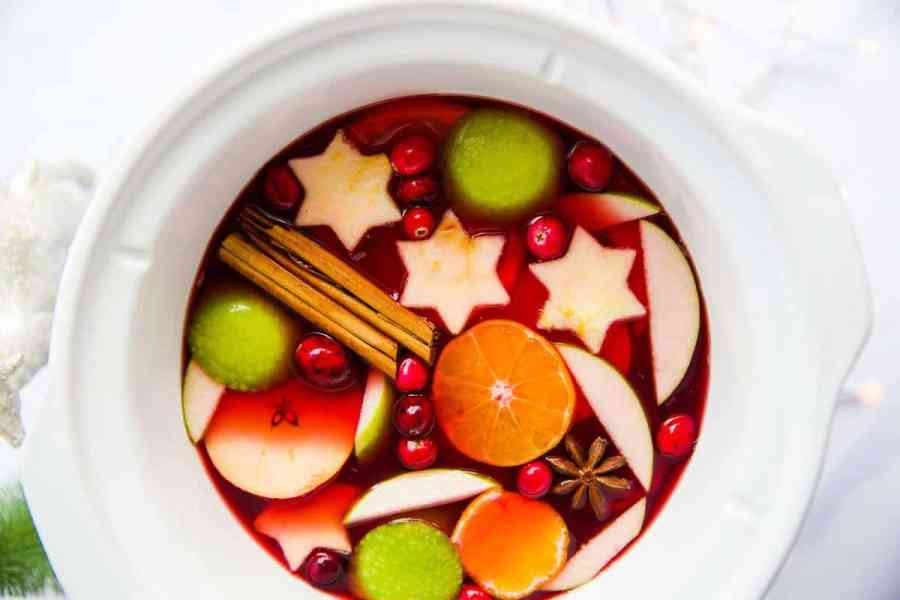 white slow cooker filled with warm Christmas punch