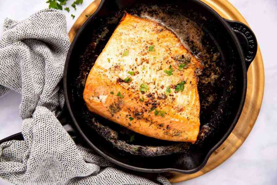 black cast iron skillet with a piece of salmon