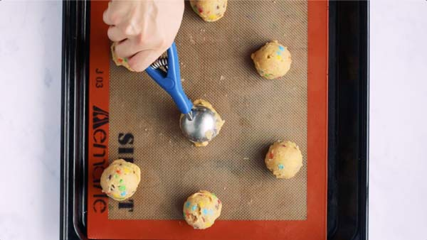 placing a cookie dough ball on a lined baking sheet