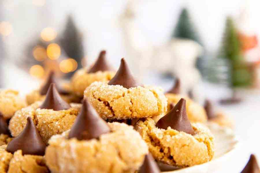 pile of peanut butter blossom cookies on a plate in front of Christmas decor