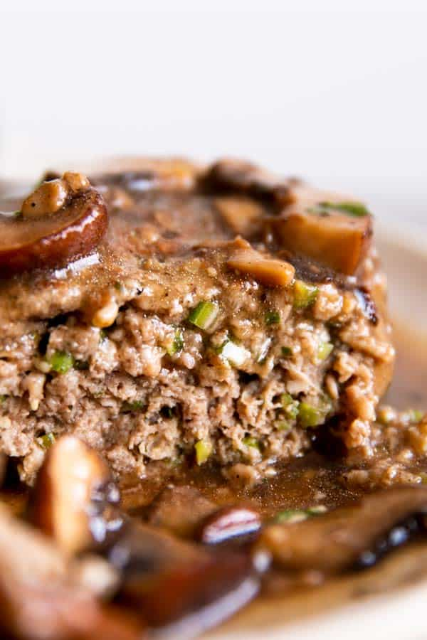 close up photo of sliced open beef patty in mushroom sauce