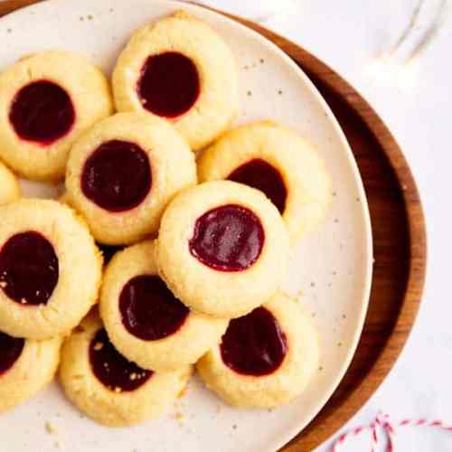white plate on a wooden platter with thumbprint cookies