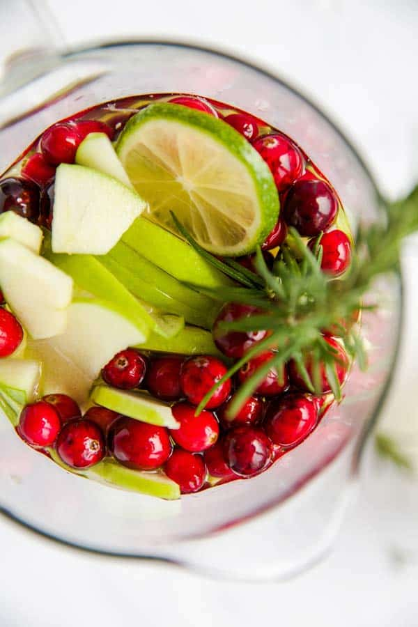 top down view on a pitcher with lime, apple, cranberries and rosemary