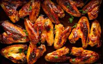 close up photo of a pan filled with sticky glazed chicken wings