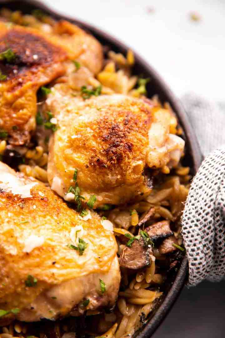 close up photo of browned chicken thigh on top of mushroom orzo