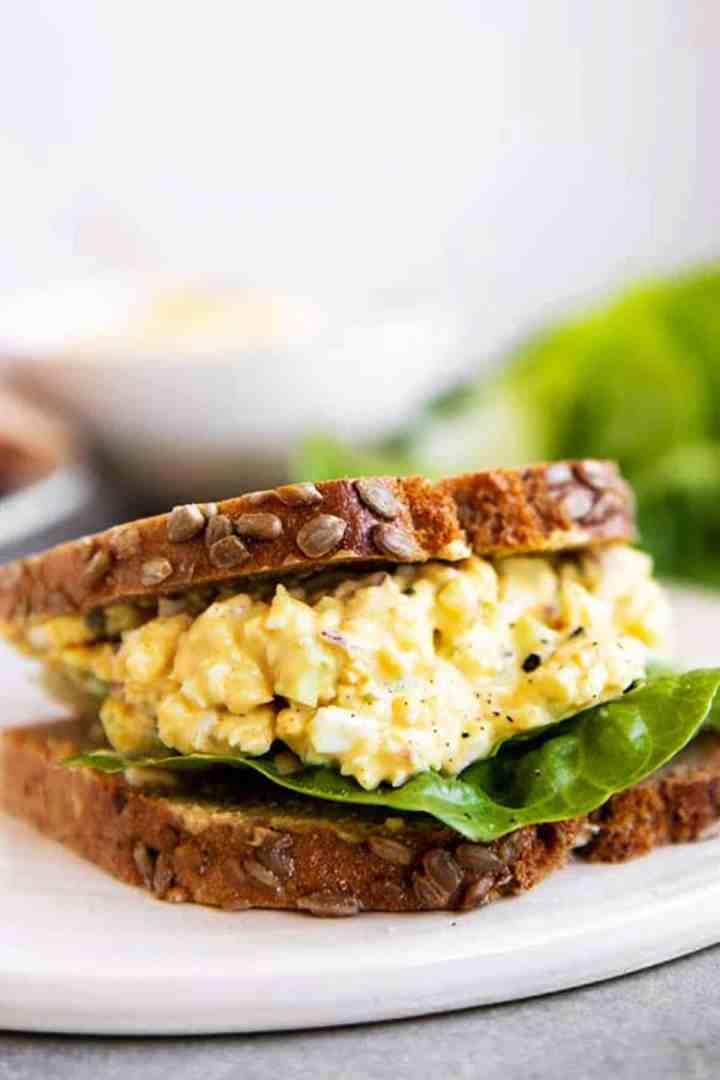 egg salad sandwich on a white platter