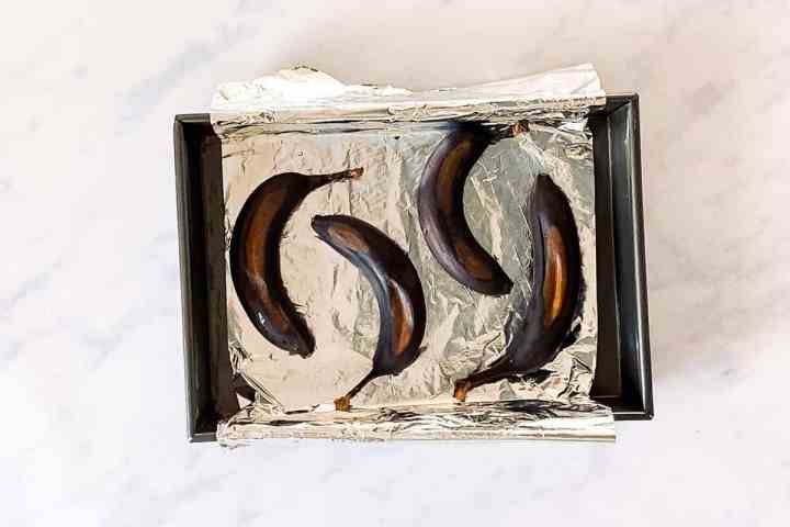 overhead view of foil lined baking pan with ripen bananas