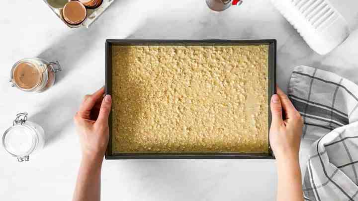 female hands holding baking pan with raw oatmeal