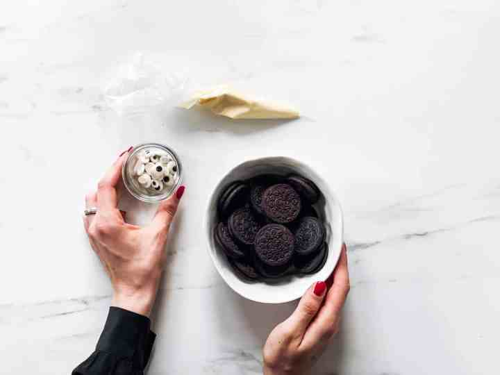 female hands holding ingredients for mummy Oreos