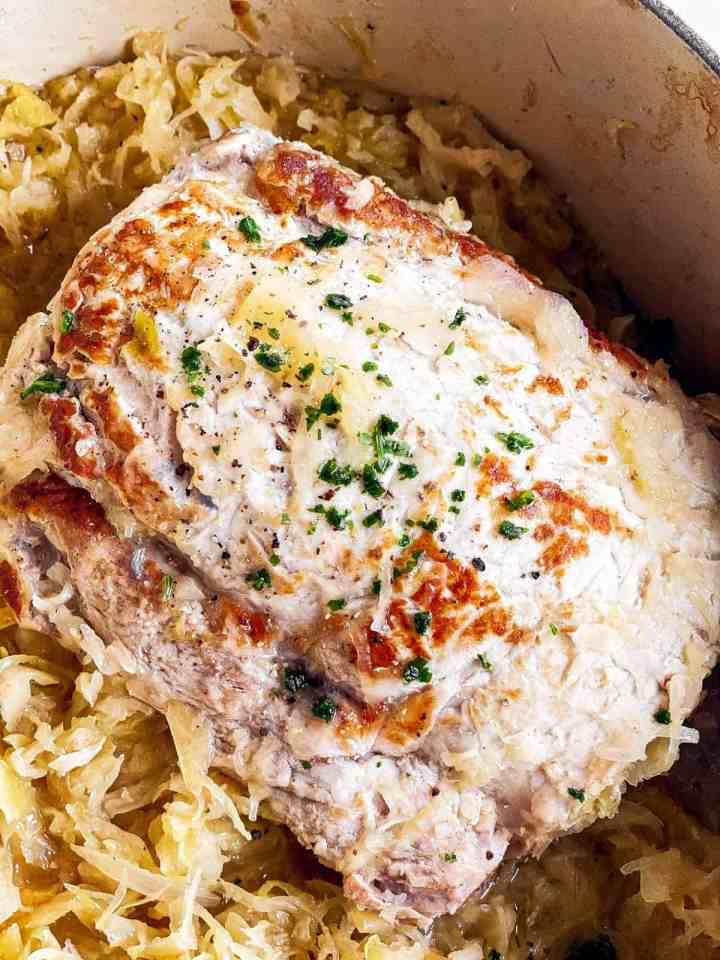 close up photo of pork roast sitting on sauerkraut