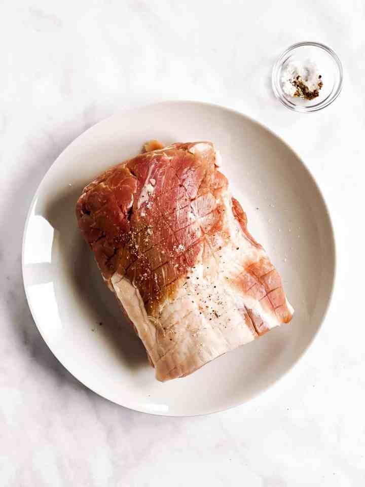 raw pork roast on white plate