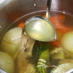 Homemade chicken stock ingredients in a stockpot with a ladle