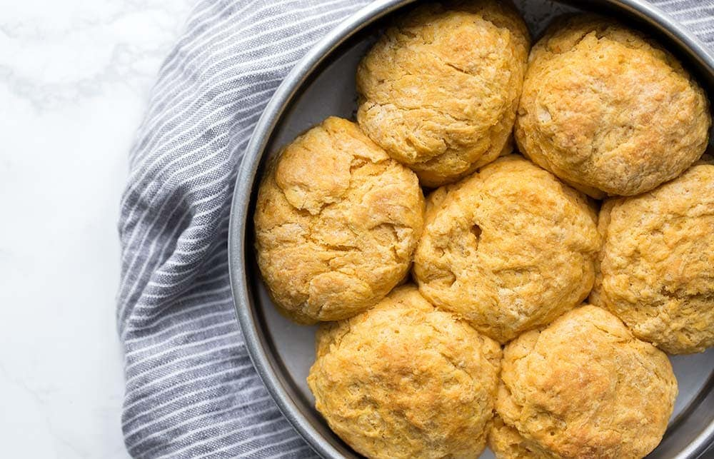 Sweet potato biscuits close together in a cake pan, fresh out of the oven.