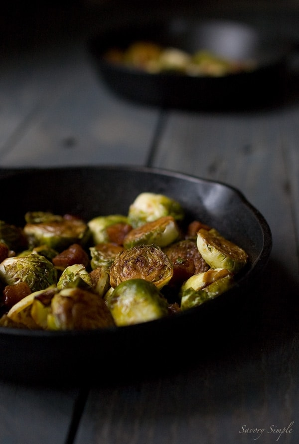 A photo of brown sugar bacon brussels sprouts in a cast iron skillet